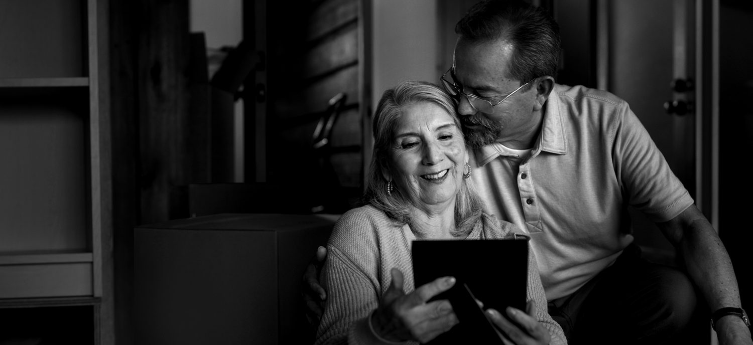 senior couple reading on tablet